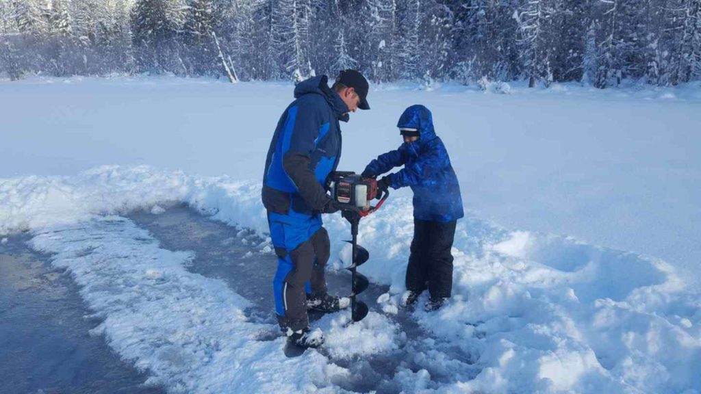 Gas powered Ice Auger drilling a hole in a frozen lake